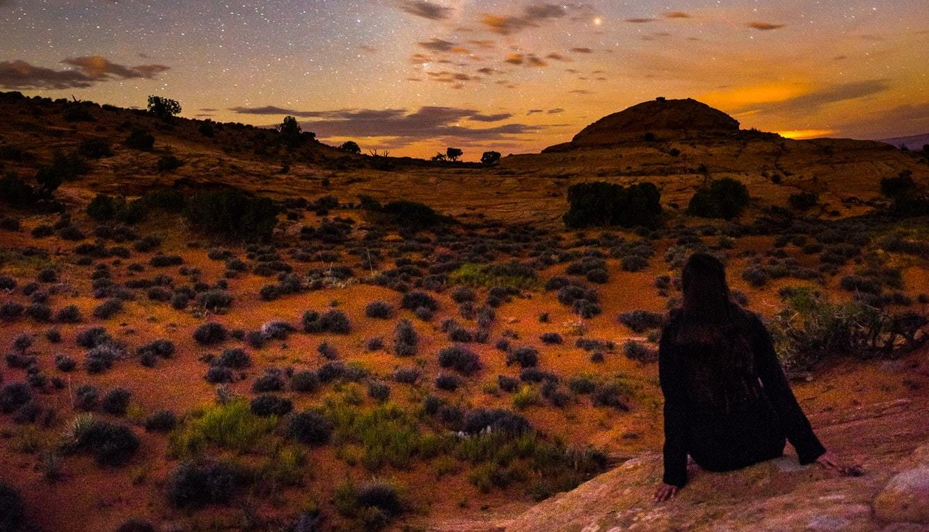 Girl Sitting on the rock looking at the Milky Way